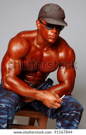 Brawny man in cap in a glasses on a light background