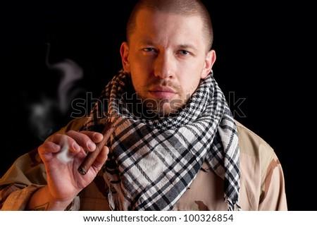 Brawny mercenary smoking cigar, over black background - stock photo