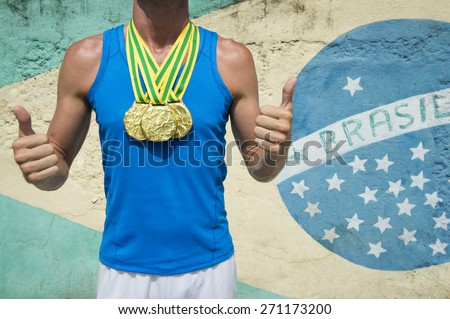 Brazil champion first place athlete wearing gold medals standing with a thumbs up in front of a Brazilian flag Rio de Janeiro  - stock photo