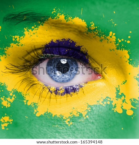 Brazil flag painted on woman face - stock photo