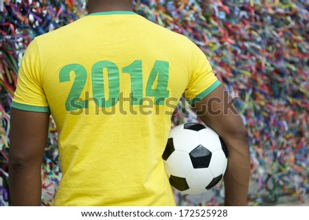 Brazil 2014 soccer player standing with football in front of wall of colorful lembranca wish ribbons in Salvador Bahia Brazil - stock photo