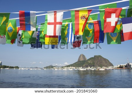 Brazilian and international flags bunting decoration above scenic sea view Sugarloaf Pao de Acucar Mountain Rio de Janeiro Brazil - stock photo