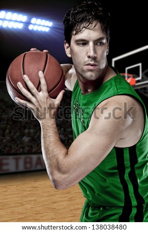Brazilian Basketball player with a ball in his hands and a green uniform. photography studio. - stock photo
