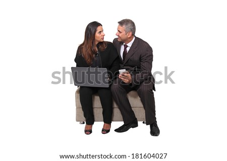 Brazilian business man holding a smartphone and woman sat holding a laptop isolated on white background.