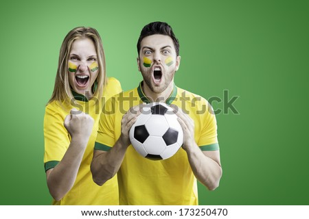 Brazilian couple celebrate on green background. Can be used as Australian uniform too. - stock photo
