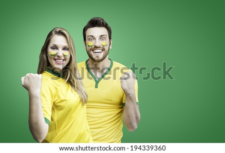 Brazilian couple fan celebrate on green background - stock photo