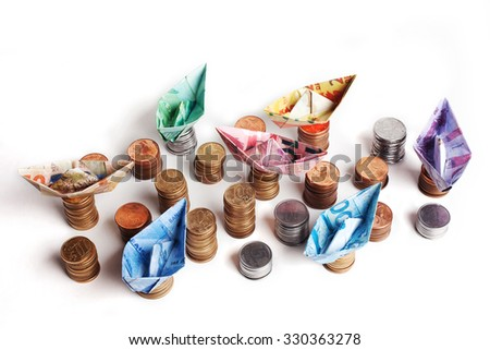 Brazilian currency coins and bill folded to sailboat. Origami art. Money from Brazil. - stock photo
