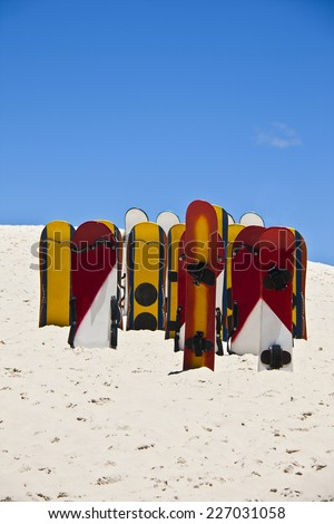 Brazilian dunes called Joaquina located in Florianopolis city in Santa Catarina state where tourists slides on dunes with sandboards that are rent there. A beautiful summer day with a clear sky on it. - stock photo