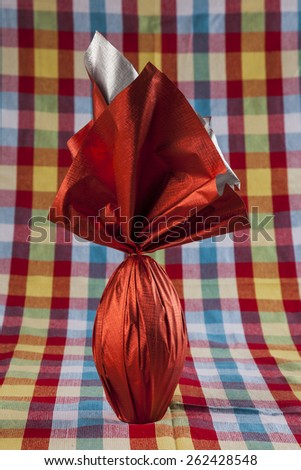 Brazilian Easters egg , wrapped in red paper, on a colored background - stock photo