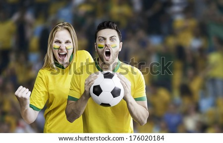 Brazilian fans celebrate on the stadium with their faces painted - stock photo