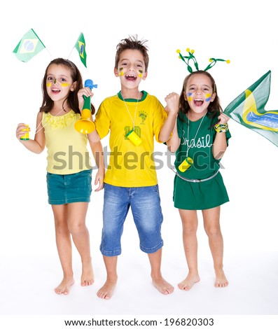 brazilian fans kids supporting brazil and wearing green and yellow clothes, with vuvuzelas and flags.