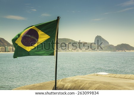 Brazilian flag against blur Copacabana Beach in Rio de Janeiro - stock photo