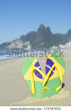 Brazilian flag flip flops sandals stuck in the sand on Ipanema Beach against a backdrop of Dois Irmaos Mountain Rio de Janeiro Brazil - stock photo