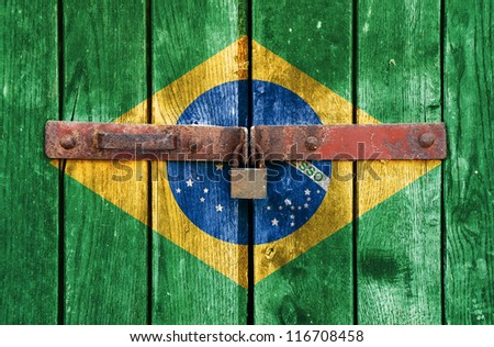 Brazilian flag on the background of old locked doors - stock photo