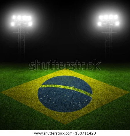 Brazilian flag painted on field with illuminated stadium lights in background - stock photo