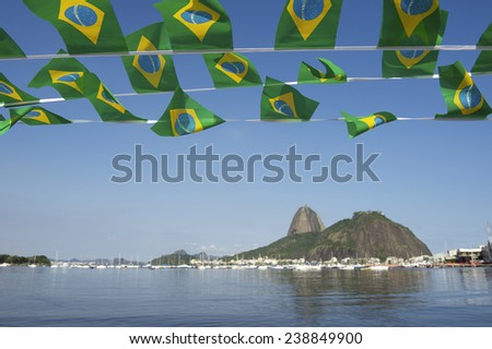 Brazilian flags bunting decoration above Botafogo Bay view of Sugarloaf Pao de Acucar Mountain Rio de Janeiro scenic skyline sea view Brazil - stock photo