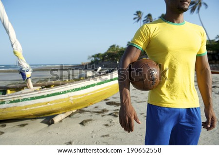 Brazilian football player in Brazil colors holding vintage soccer ball in front of fishing boat on Nordeste Brazil beach - stock photo