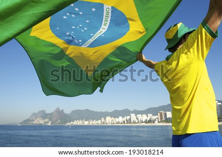 Brazilian football soccer player flying flag in front of Ipanema Beach city skyline Rio de Janeiro Brazil - stock photo