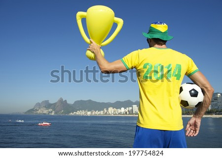 Brazilian footballer in 2014 shirt in team Brazil colors celebrating with trophy and soccer ball on tropical Ipanema Beach Rio de Janeiro