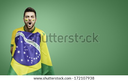 Brazilian man celebrates on green background - stock photo