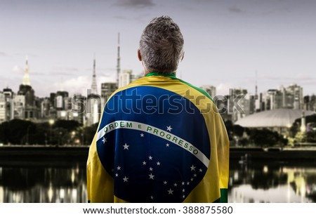Brazilian man holding the flag of Brazil in Sao Paulo - stock photo