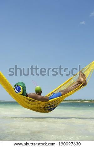 Brazilian man relaxing in beach hammock drinking fresh coconut water  - stock photo