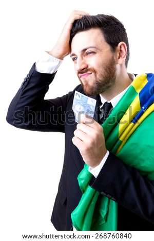 Brazilian not so happy holding Brazilian money and the flag of Brazil - stock photo