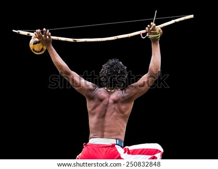 Brazilian performing Capoeira with Berimbau Instrument isolated on black background - stock photo