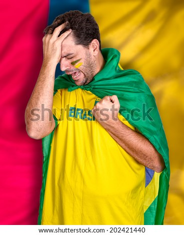 Brazilian soccer fan or supporter crying in the championship or competition or cup. - stock photo
