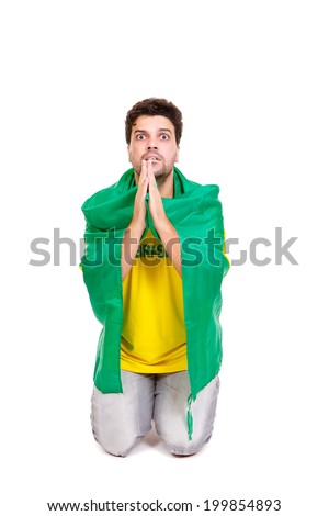Brazilian soccer fan or supporter worried and praying in the championship or competition or cup.