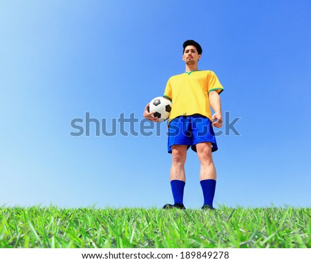 Brazilian soccer football player man holding ball at the stadium with blue sky