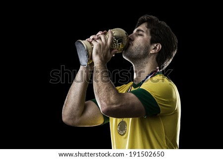 Brazilian soccer player, celebrating the championship with a trophy in his hand, on a black background. - stock photo
