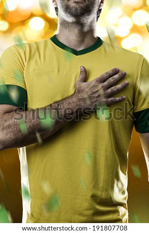 Brazilian soccer player, listening to the national anthem with his hand on his chest, on a yellow background. - stock photo