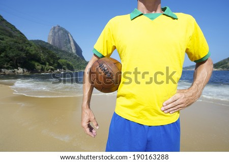 Brazilian soccer player standing with old football at Praia Vermelha Red Beach in front of Sugarloaf Pao de Acucar Mountain in Rio de Janeiro Brazil