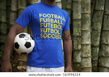 Brazilian soccer player wears international football shirt against a tropical bamboo forest background - stock photo