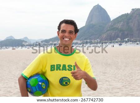 Brazilian sports fan with ball at Rio de Janeiro showing thumb up - stock photo