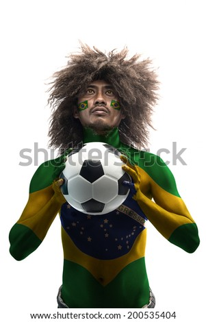 Brazilian supporter holding a soccer ball  with the flag of the Brazil painted on body - stock photo
