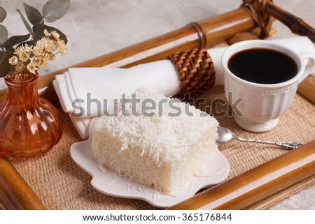 Brazilian traditional dessert: sweet cuoscous (tapioca) pudding (cuscuz doce) with coconut and cup of coffee. Selective focus