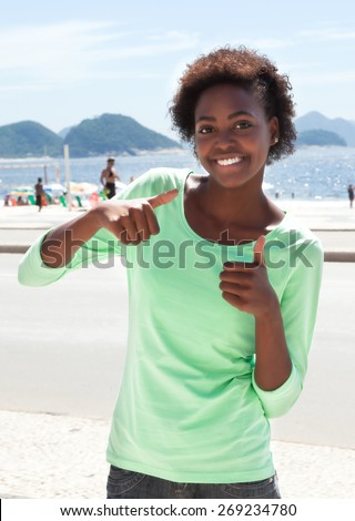Brazilian woman at Copacabana beach showing thumbs - stock photo