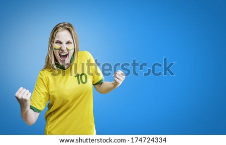 Brazilian woman celebrates on blue background with her face painted. Can be used as Australian uniform too. - stock photo