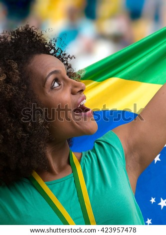 Brazilian woman fan holding the Brazilian flag in the stadium