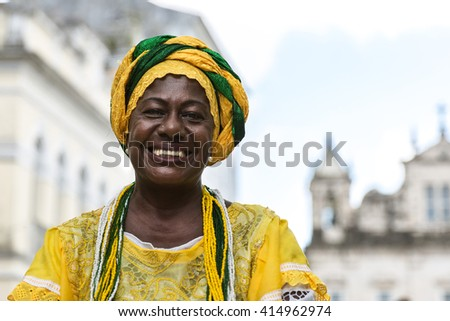 Brazilian woman of African descent wearing traditional clothes from the state of Bahia in the old colonial district of Salvador (Pelourinho). - stock photo