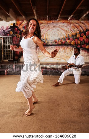 Brazillian dancer and pandeiro drummer performing indoors - stock photo