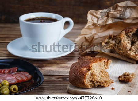 Bread, a cup of coffee , ham and olives on a wooden table lie.Focus concept.