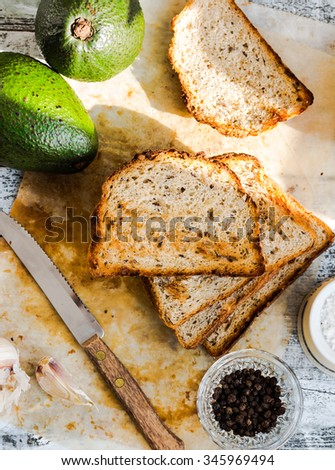 bread and a whole avocado with cherry tomatoes, pepper and garlic, a set of products to toast, snack - stock photo