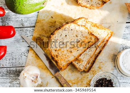 bread and a whole avocado with pepper and garlic, a set of products to toast,top view - stock photo