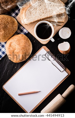 Bread and blank clipboard with coffee on black background