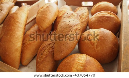 Bread and buns in basket on shelf in bakery or baker's shop - stock photo
