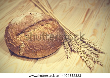 Bread and ears of wheat on a wooden table, rustic style, closeup