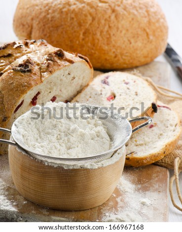 Bread and flour on wooden table. Selective focus
